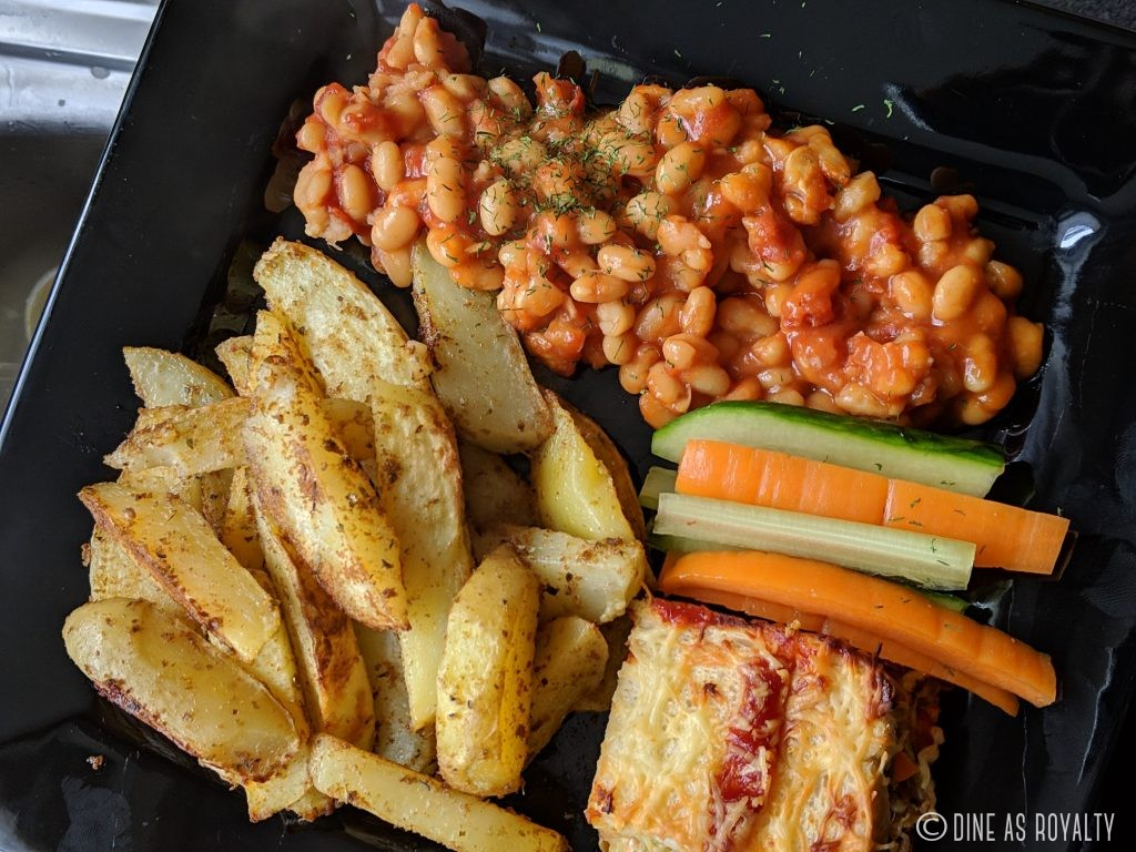 Yaji potatoes with baked beans, a slice of ajekusine casserole and fresh veggies.